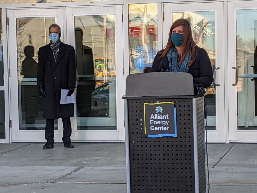 Person standing at a podium wearing a mask