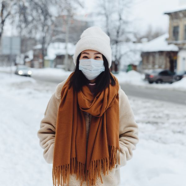 A person stands outside in the snow with a mask on
