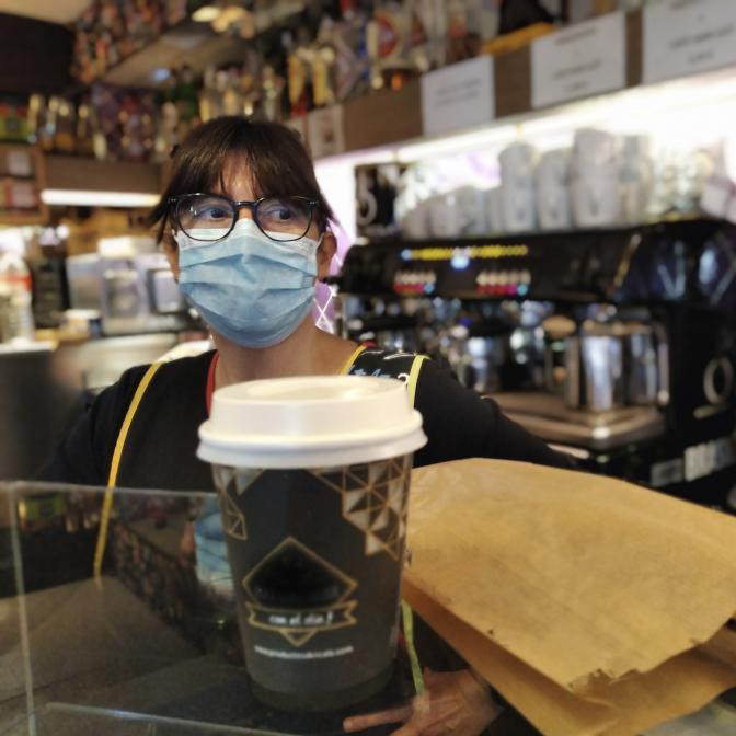 A barista is working at a coffee shop and hands someone their order while wearing a mask