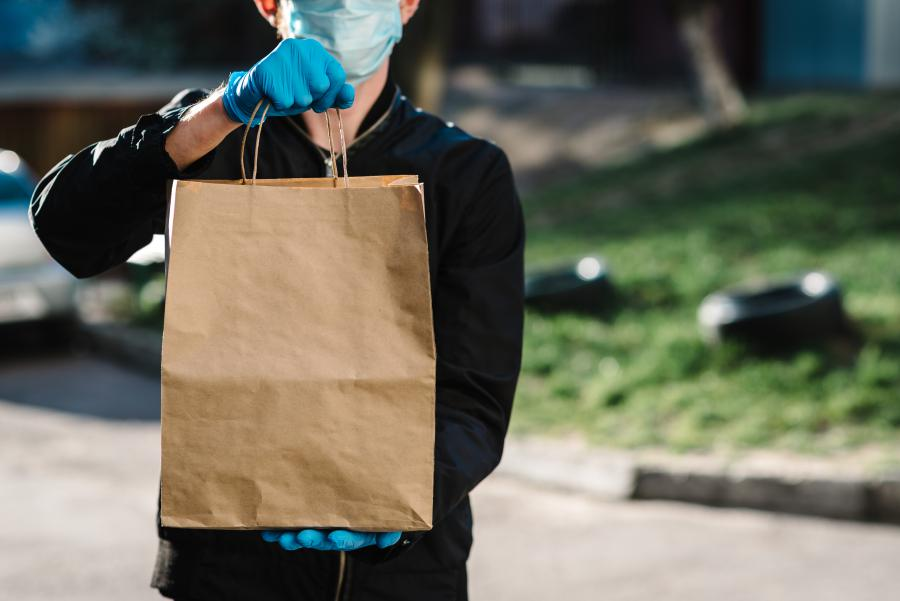 Delivery person with mask and gloves holding an order of food