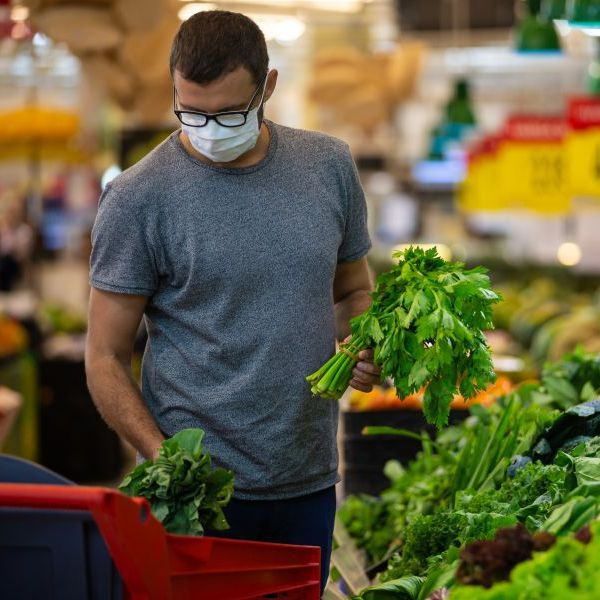A person wears a mask and picks out greens at a grocery store