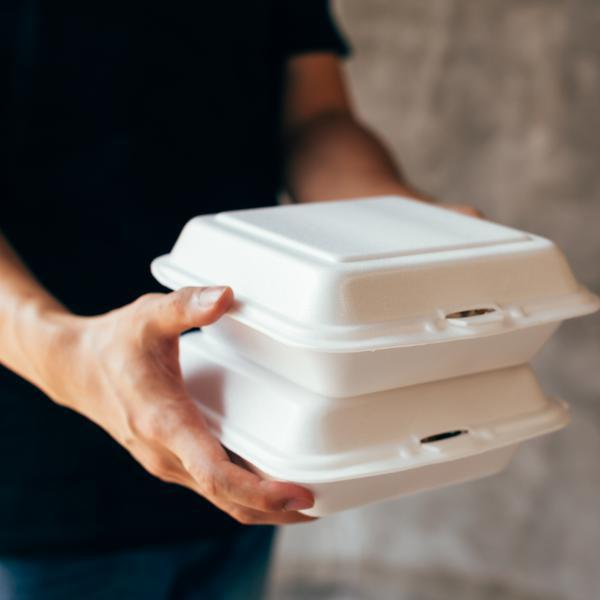 person holding takeout containers