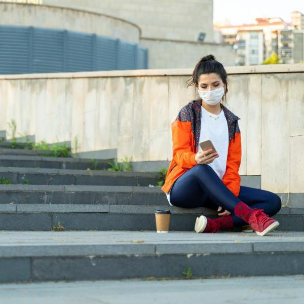 Young adult looking at phone while sitting on steps outside. They are wearing a mask.