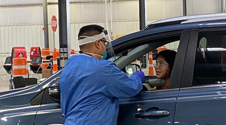 A person sitting in a vehicle speaking to a man in scrubs preparing for a drive-through COVID-19 test.