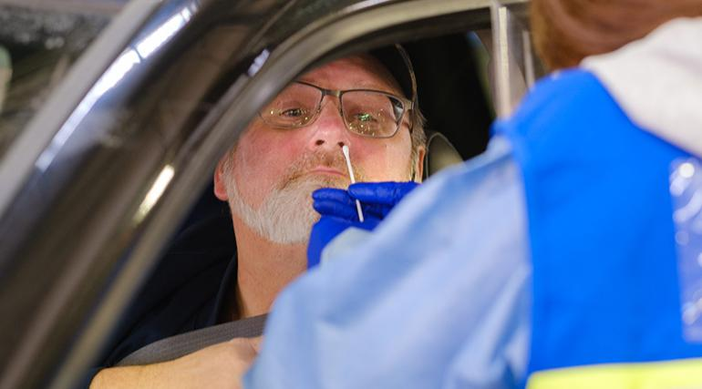 A bearded man in a vehicle getting a COVID-19 swab test