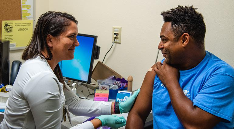 A nurse smiling at a patient while prepping his his arm for an injection. Photo by Will Cioci, City of Madison
