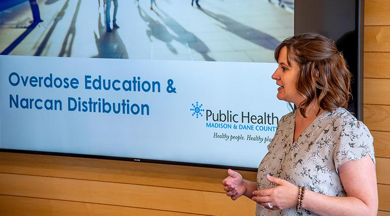 Public Health employee giving a presentation with a slide in the background
