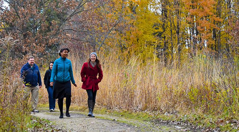 A group of 4 people walking on a trail in the UW Arboretum with fall colors in the background.