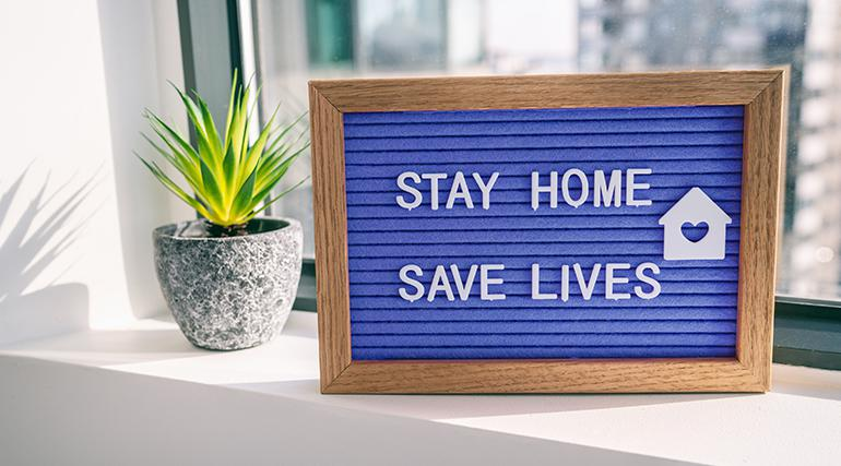 "A blue sign board sign board sits on in a window next to a potted plant. The sign displays the text ""Stay Home, Save Lives""."