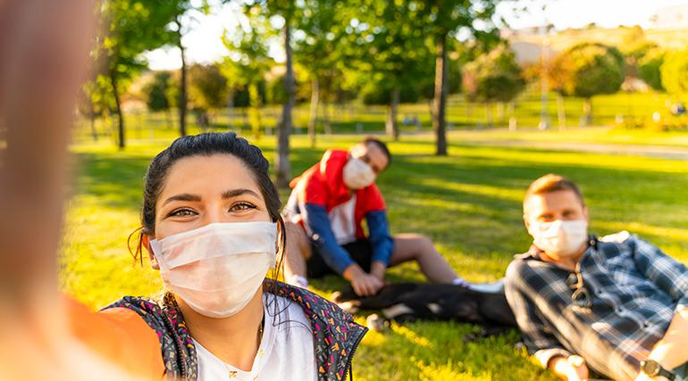 Young woman taking a selfie with three friends in a sun-lit green park. Each is wearing a mask and maintaining a safe distance.