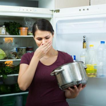 Woman standing in front of open refrigerator with cooking pot in hand, holding hand over nose