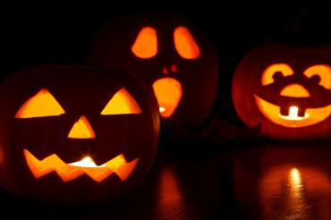 Three carved Halloween pumpkins at night