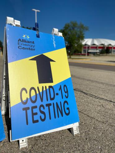 Sign with arrow that says COVID-19 testing with Dane County Coliseum in background
