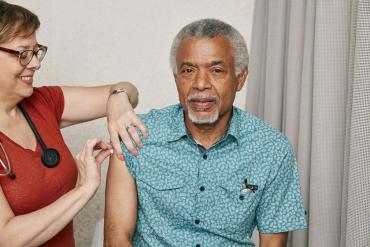 A man, sitting down, getting a vaccination from a woman, who is standing